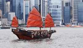 An antique boat with red sails on the water in Singapore