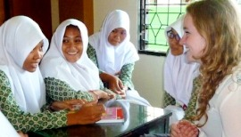 A young girl talks to Indonesian students visiting their school