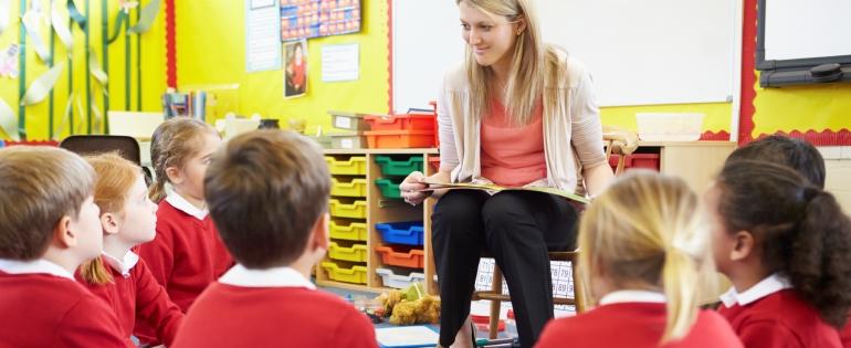 A female teacher reads to her class
