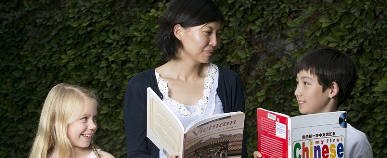 Mother with two children reading books about learning Asian languages