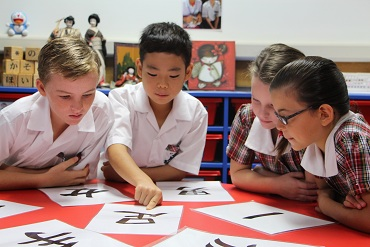 Four children in classroom looking at Asian characters on laminated A4 paper
