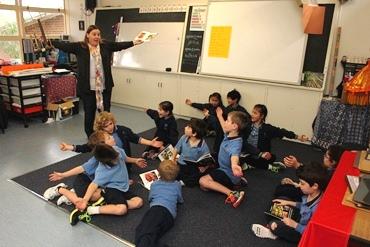 A teacher demonstrates a gesture to her class