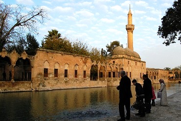 Men and women in Urfa, Turkey, standing by the river which runs alongside a mosque