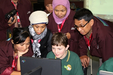 Students and teachers at computer working collaboratively
