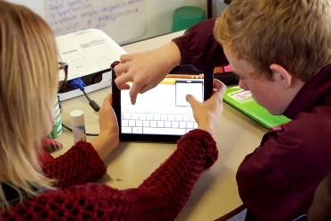 A teacher and student work on an iPad together