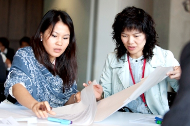 Two women work together at the AEF conference