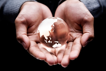 A pair of hands hold a small globe of the world