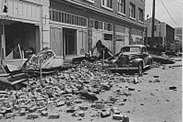 A black and white photo of rubble in a street after an accident
