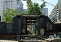 A collapsed Ancient building entrance remains in ruins in between highrise apartment buildings