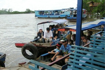 People travel down the Mekong River on wooden boats