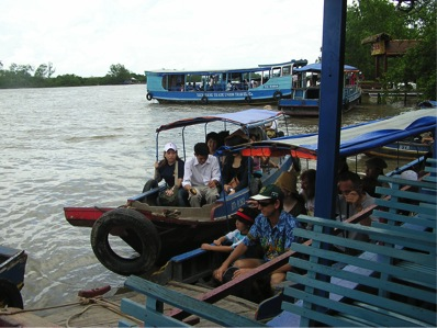 Boats filled with people being transported along the Mekong River
