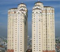 Two high-rise apartment buildings next door to each other, towering over the city below