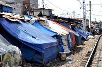 Homes with plastic tarpaulins as roofs, next to the train tracks