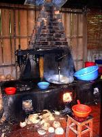 A stove with discarded coconut shells, pans, and bowls lying around during coconut toffee production