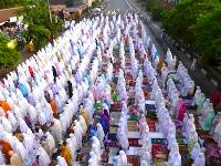 Hundreds of people congregating for a morning religious service, all dressed in colourful burqas