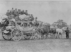 Black and white image of Chinese migrants on stagecoach led by horses