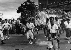 A black and white photograph of a parade with Chinese dragon