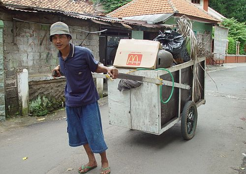 A man pulls a cart laden with rubbish down a street in Jakarta