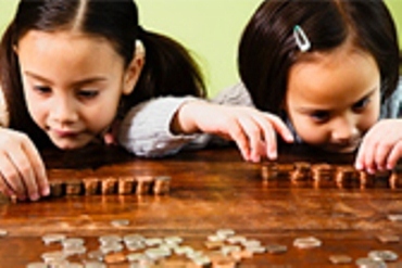 Two girls sit and count coins