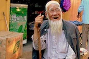 An old man, smiling with his walking stick sit on a stool
