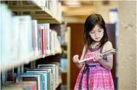 Young girl selecting a book from a library shelf