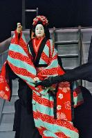A female Sanbaso Bunraku puppet wearing a red kimono being manipulated by 2 puppeteers