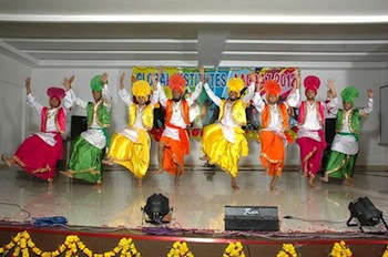 Colourfully costumed male dancers performing the Bhangra dance