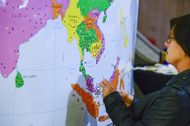 Woman putting a sticker on a map of Asia