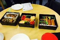 Three Japanese bento boxes with food on table