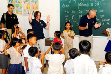 Visiting adults play games with children at a school in Cambodia