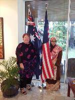 Two women standing next to an Australian and a Malaysian flag