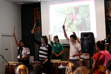 Students perform using drums